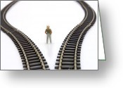Pondering Greeting Cards - Figurine between two tracks leading into different directions  symbolic image for making decisions. Greeting Card by Bernard Jaubert