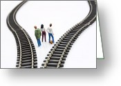 Contemplating Greeting Cards - Figurines between two tracks leading into different directions symbolic image for making decisions. Greeting Card by Bernard Jaubert