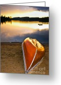 Setting Greeting Cards - Lake sunset with canoe on beach Greeting Card by Elena Elisseeva
