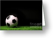 Soccer Stadium Greeting Cards - Soccer ball on grass against black Greeting Card by Sandra Cunningham