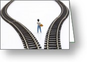 Figurine Greeting Cards - Figurine between two tracks leading into different directions symbolic image for making decisions. Greeting Card by Bernard Jaubert