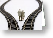 Senior Greeting Cards - Figurines between two tracks leading into different directions symbolic image for making decisions. Greeting Card by Bernard Jaubert