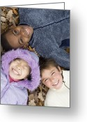 Multicultural Greeting Cards - Smiling Children Lying On Autumn Leaves Greeting Card by Ian Boddy
