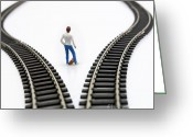 Young Teen Greeting Cards - Figurine between two tracks leading into different directions symbolic image for making decisions. Greeting Card by Bernard Jaubert