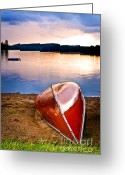 Vivid Greeting Cards - Lake sunset with canoe on beach Greeting Card by Elena Elisseeva