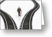 Pensive Greeting Cards - Figurine between two tracks leading into different directions symbolic image for making decisions. Greeting Card by Bernard Jaubert