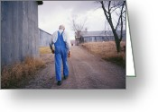 Structures Greeting Cards - An Elderly Farmer In Overalls Walks Greeting Card by Joel Sartore