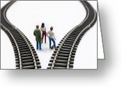 Pensive Greeting Cards - Figurines between two tracks leading into different directions symbolic image for making decisions. Greeting Card by Bernard Jaubert
