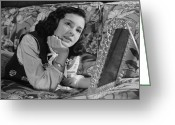 Chin Up Greeting Cards - Girl (8-9) Lying On Couch, Holding Framed Photo , (b&w) Greeting Card by George Marks