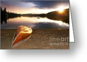 Boat Greeting Cards - Lake sunset with canoe on beach Greeting Card by Elena Elisseeva