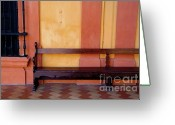 Royalty Greeting Cards - Long wooden bench against a yellow wall at the Alcazar of Seville Greeting Card by Sami Sarkis