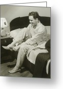 Pajamas Greeting Cards - Mature Man Sitting On Bed Putting On Slippers, Smiling Greeting Card by George Marks