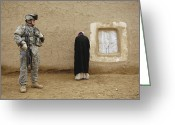 Villagers Greeting Cards - U.s. Army Specialist Guards An Iraqi Greeting Card by Stocktrek Images