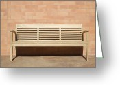 Empty Park Bench Greeting Cards - Wooden Bench Set Against Brick Wall Greeting Card by Jeremy Woodhouse