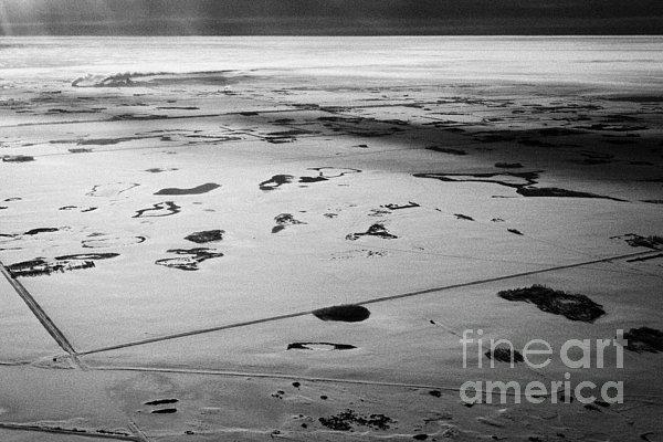 aerial view of snow covered prairies and remote isolated farmland in Saskatchewan Canada Print by Joe Fox