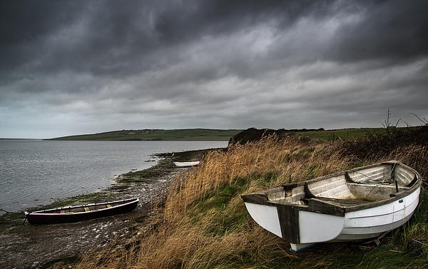 Old Decayed Rowing Boats On Shore Of Lake With Stormy Sky Overhe Print by Matthew Gibson