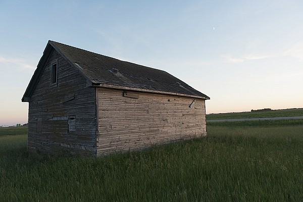 A Wooden Shed In The Middle Of A Grass Print by Keith Levit