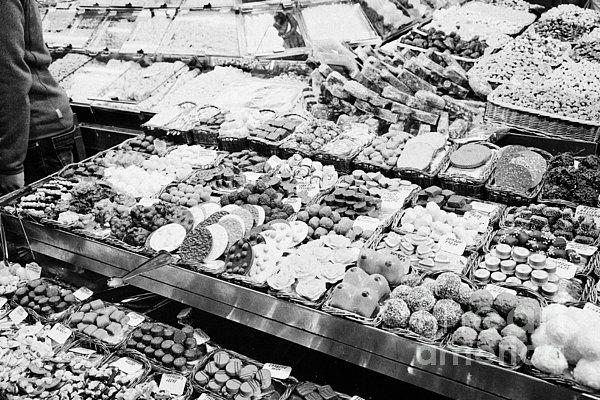 chocolates on display inside the la boqueria market in Barcelona Catalonia Spain Print by Joe Fox
