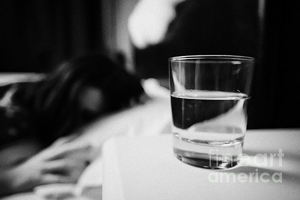 Glass Of Water On Bedside Table Of Early Twenties Woman In Bed In A Bedroom Print by Joe Fox