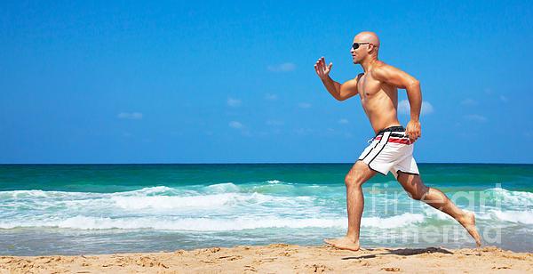 Healthy Man Running On The Beach Print by Anna Omelchenko