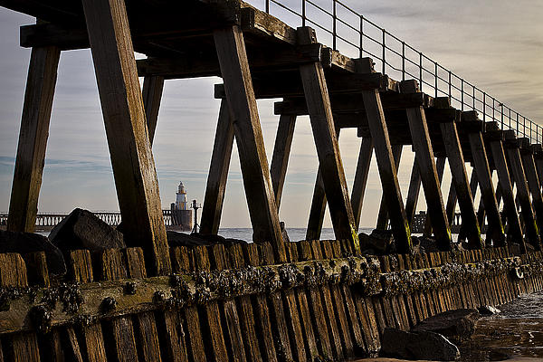Lighthouse Through The Wooden Pier Print by Jim Jones