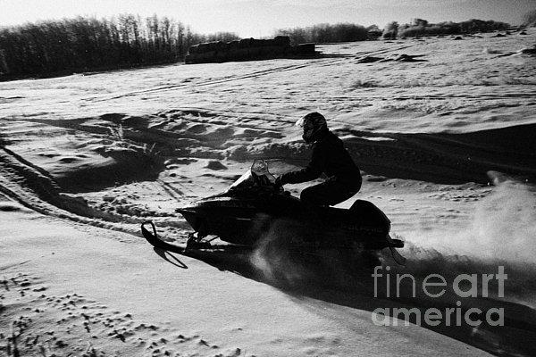 man on snowmobile crossing frozen fields in rural Forget Saskatchewan Print by Joe Fox