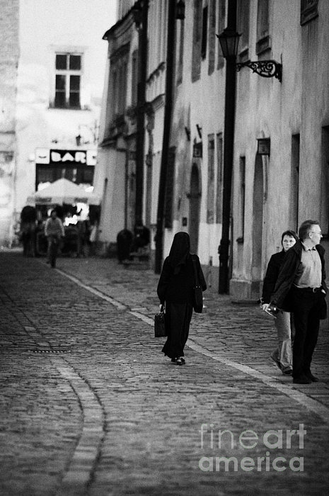 nun with briefcase walking up cobblestone street Kanonicza past tourists in old town krakow Print by Joe Fox