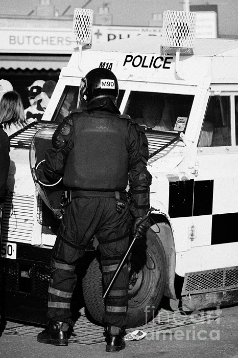 Psni Officer With Riot Gear And Baton In Front Of Land Rover On Crumlin Road At Ardoyne Shops Belfas Print by Joe Fox