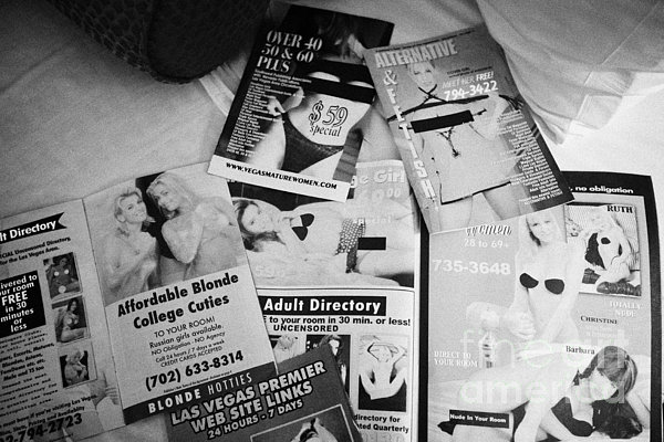 selection of leaflets advertising girls laid out on a hotel bed in Las Vegas Nevada USA Print by Joe Fox