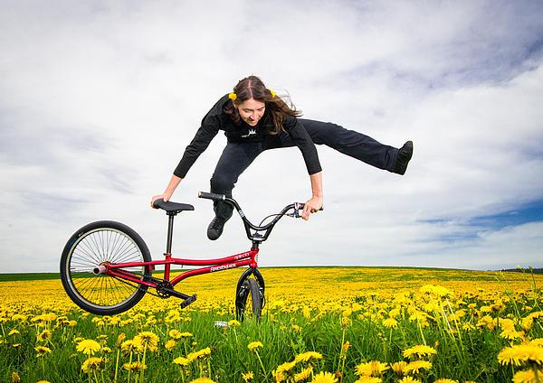 Spring Has Sprung - Bmx Flatland Artist Monika Hinz Jumping In Yellow Flower Meadow Print by Matthias Hauser