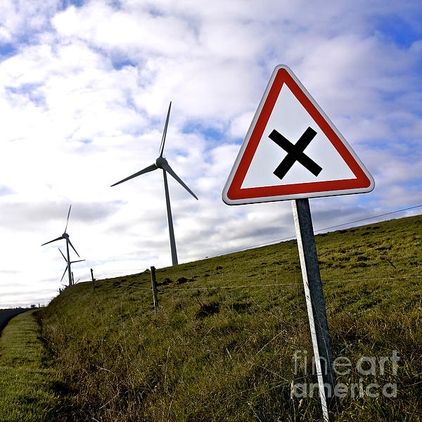 Wind Turbines On The Edge Of A Field With A Road Sign In Foreground. Print by Bernard Jaubert
