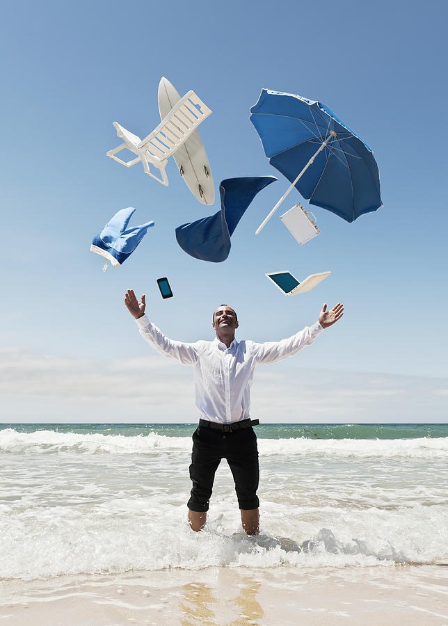 A Man Stands In The Ocean With Items Photograph
