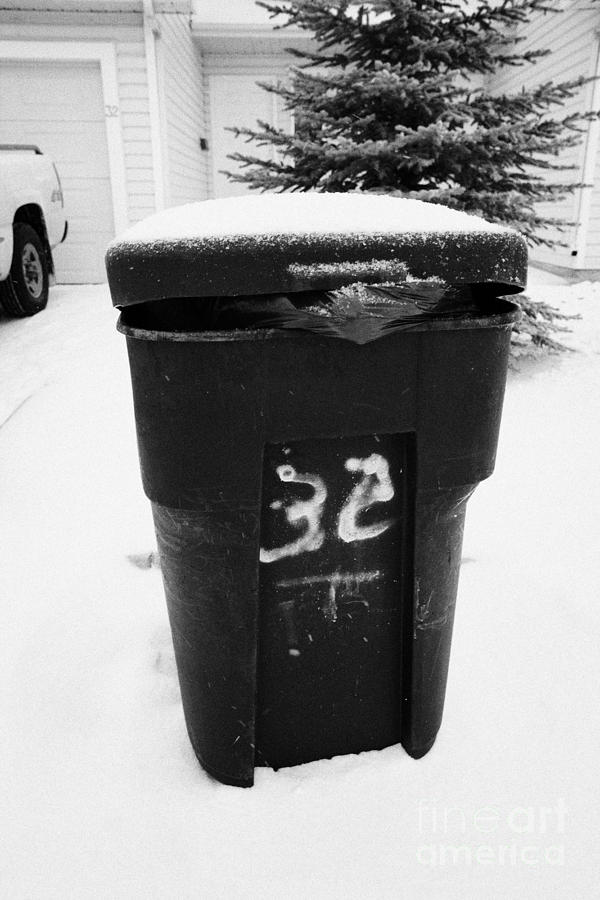 bag sticking out of litter waste bin covered in snow outside house in Saskatoon Saskatchewan Canada Photograph