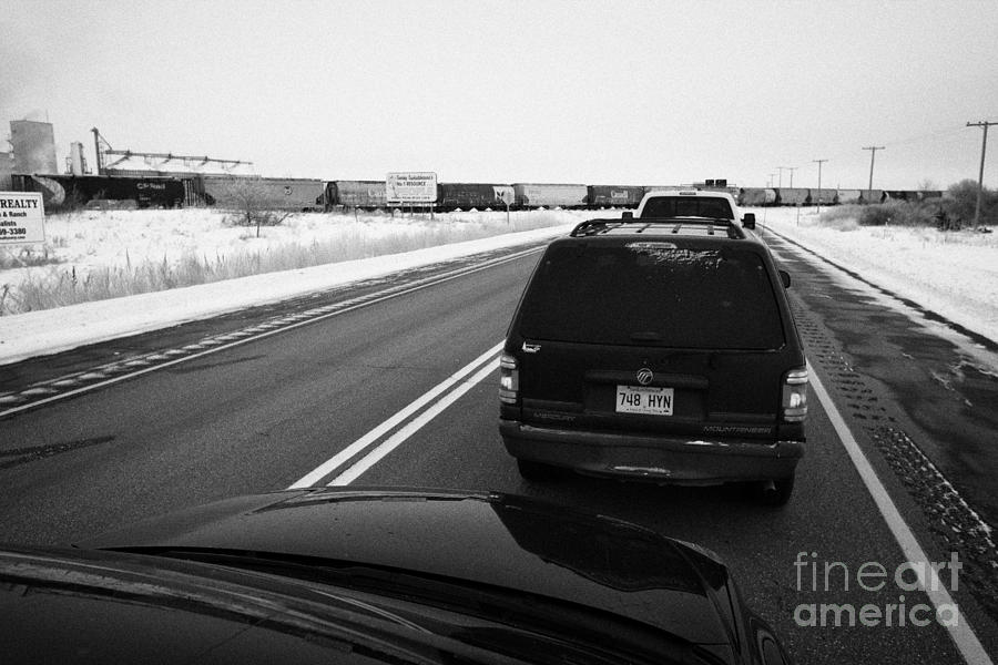 cars waiting on train crossing trans-canada highway in winter outside Yorkton Saskatchewan Canada Photograph