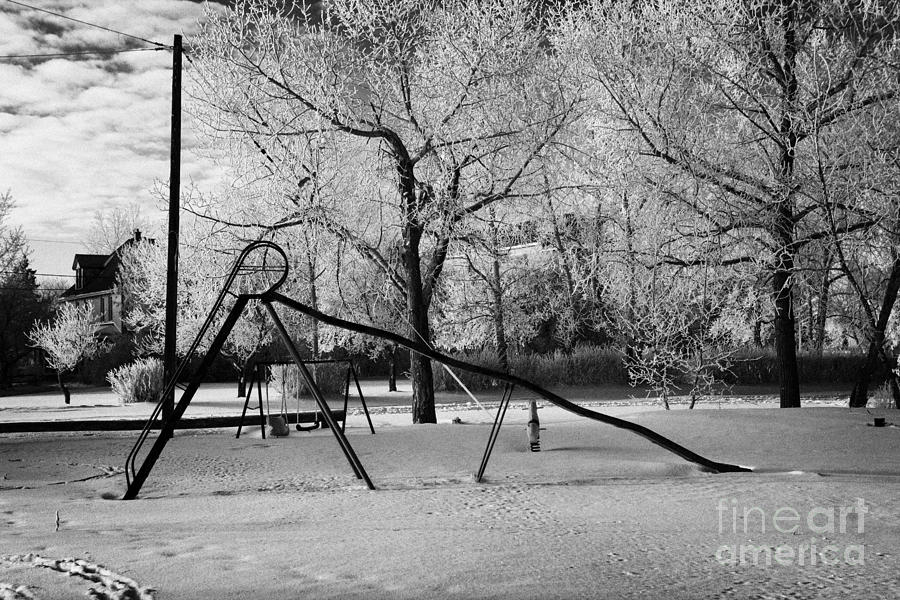 empty childrens playground with hoar frost covered trees on street in small rural village of Forget  Photograph  - empty childrens playground with hoar frost covered trees on street in small rural village of Forget  Fine Art Print