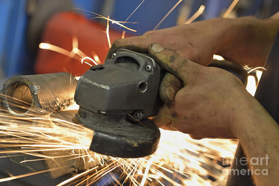 Man Cutting Steel With Grinder Photograph