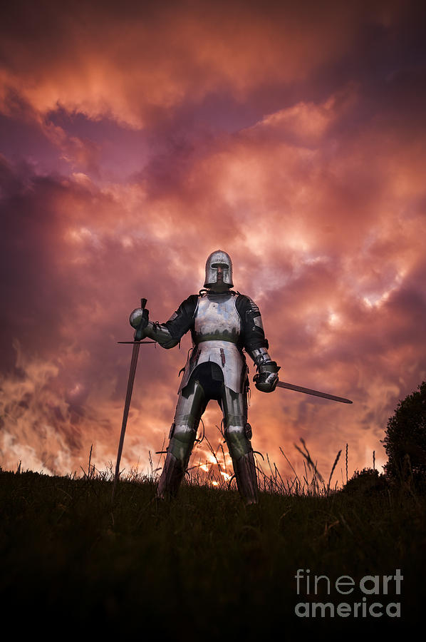 Medieval knight in armour on a burning battlefield photograph