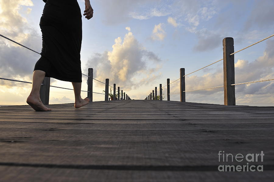 Woman Walking On Wooden Jetty At Sunrise Photograph