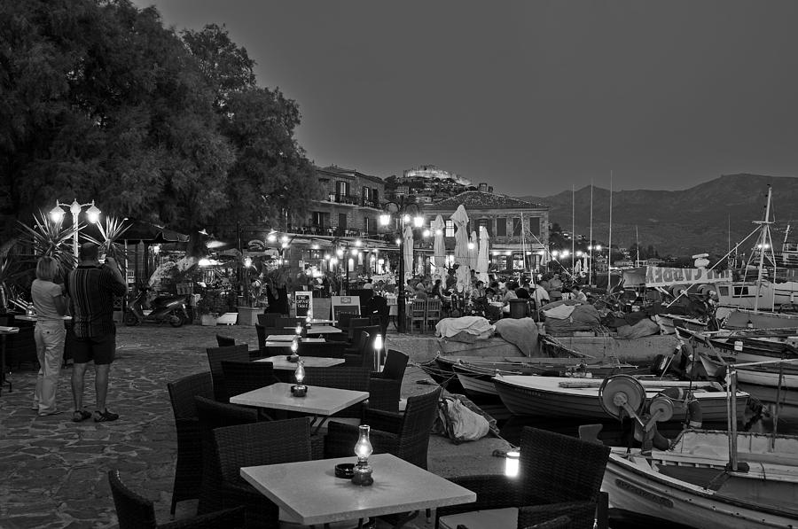 Lesvos; Lesbos; Molyvos; Molivos; Mithimna; Mithymna; Village; Town; Port; Harbor; People; Tourists; Man; Woman; Castle; Fortress; Boat; Boats; Fishing; Island; Greece; Hellas; Aegean; Summer; Holidays; Vacation; Tourism; Touristic; Travel; Trip; Voyage; Journey; Dusk; Twilight; Night; Tables; Chairs; Bar; Pub; Inn; Black And White; Black + White; B/w; B&w; B+w; Islands Photograph - Molyvos Village by George Atsametakis