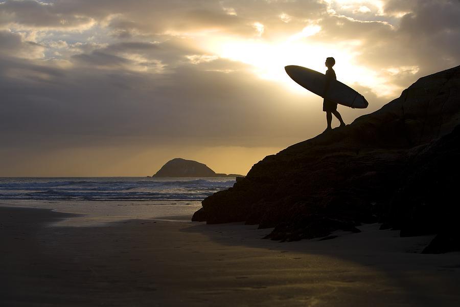 Journey Photograph - A Surfer On Muriwai Beach New Zealand by Deddeda