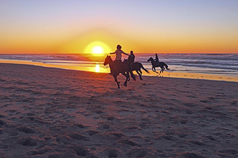 Couple horse riding on the beach