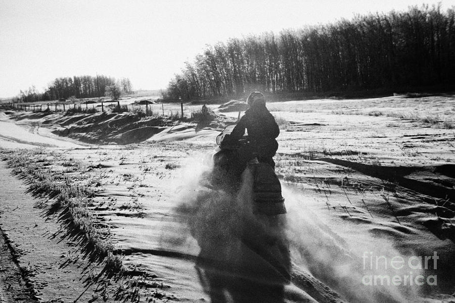 man on snowmobile crossing frozen fields in rural Forget Saskatchewan Canada Photograph