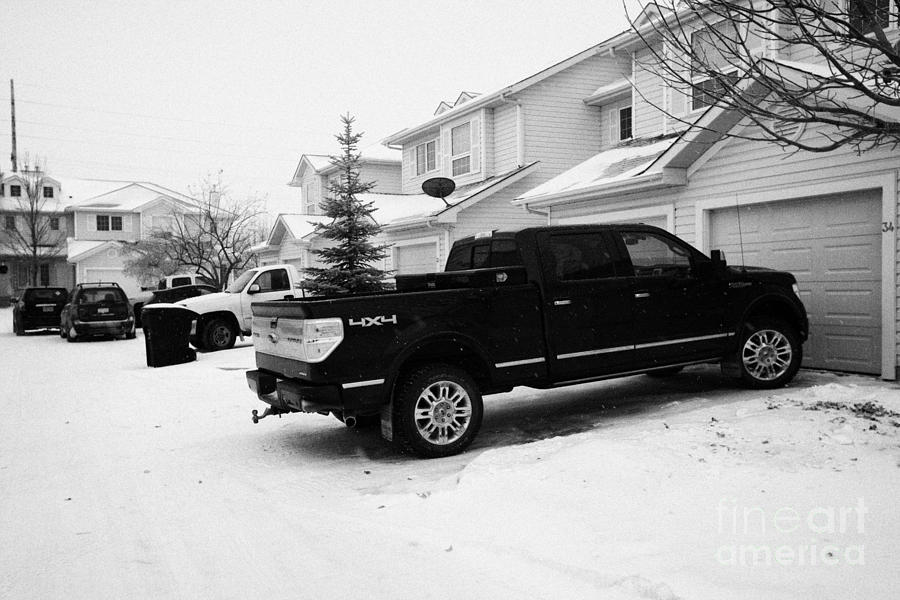4x4 Pickup Trucks Parked In Driveway In Snow Covered Residential Street During Winter Saskatoon Sask Photograph  - 4x4 Pickup Trucks Parked In Driveway In Snow Covered Residential Street During Winter Saskatoon Sask Fine Art Print