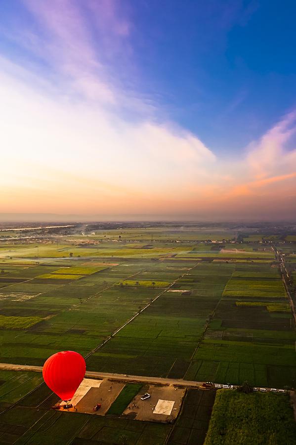 A Red Hot Air Balloon Landing In Egyptian Fields Photograph