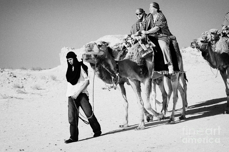 bedouin guide in modern clothing leads british tourists riding camels and wearing desert clothes into the sahara desert at Douz Tunisia Photograph