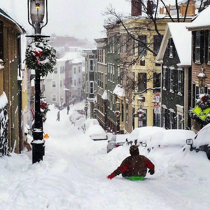Guy sledding down a street in Charlestown, Massachusetts
