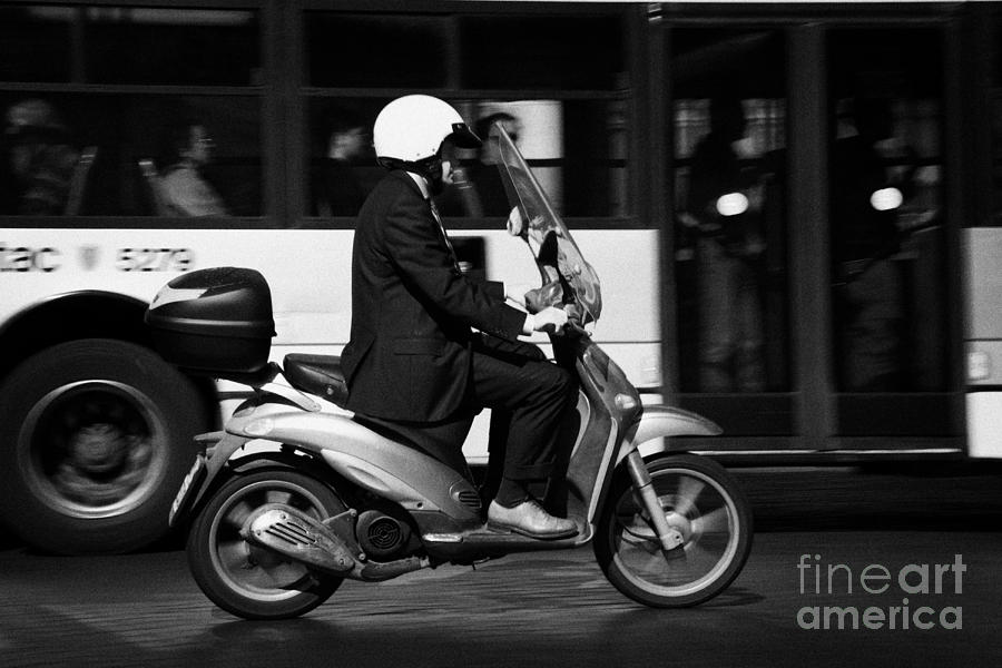 Business Man In Suit And White Helmet On Scooter Commutes Past Bus Full Of Passengers Through Piazza Photograph