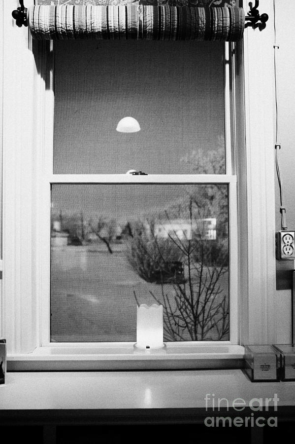 Candle In The Window Looking Out Over Snow Covered Scene In Small Rural Village Photograph