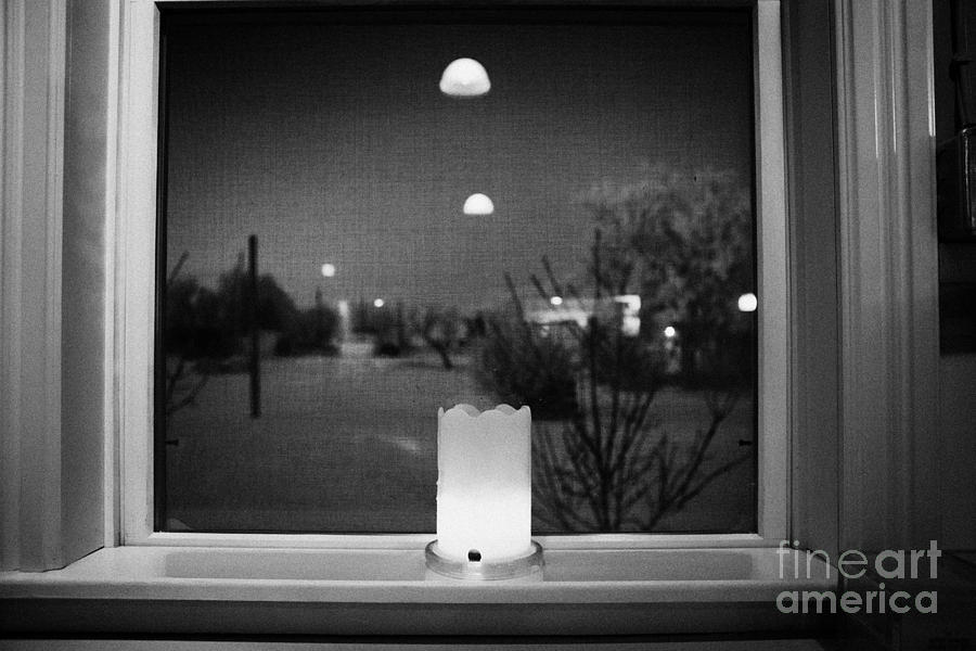 candle in the window looking out over snow covered scene in small rural village of Forget Saskatchew Photograph