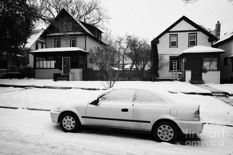 car covered in snow parked by the side of the street in front of residential homes caswell hill Sask Photograph